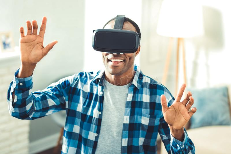 Optimistic young afro american man playing game. Game in VR. Joyful afro american man putting on VR glasses and launching app royalty free stock photography