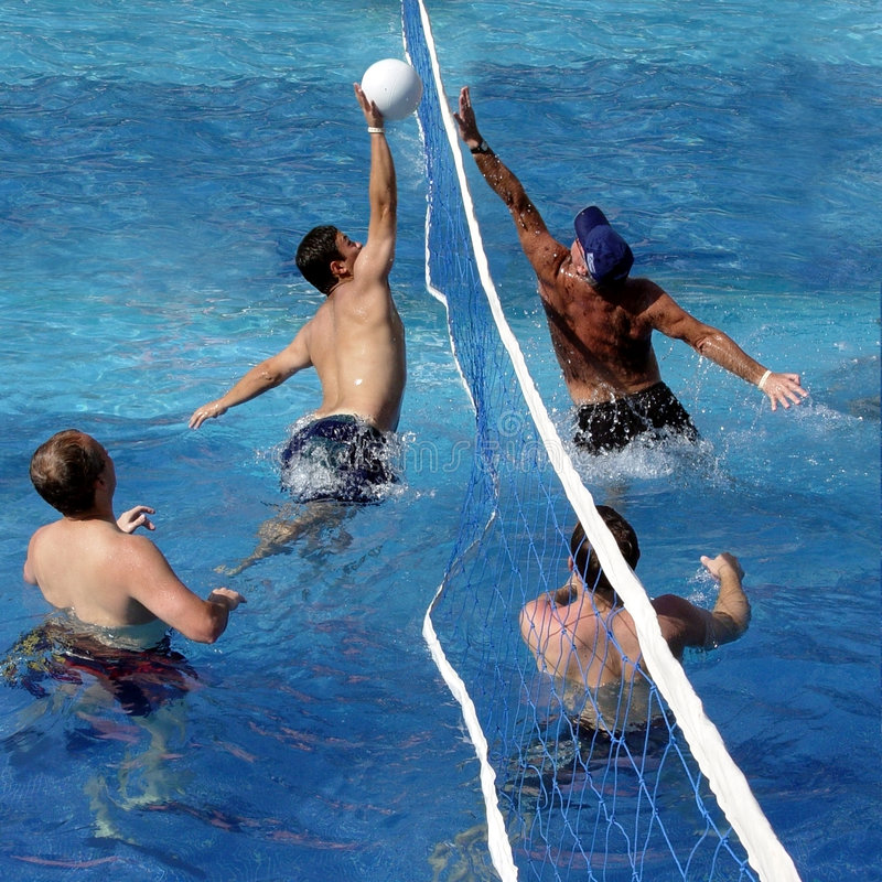 Game of water polo. 4 men playing water polo in a swimming pool