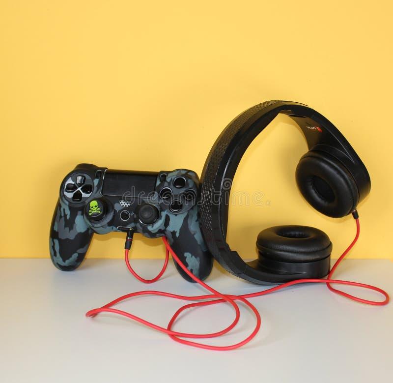 Gamecontroller mit Kopfhörerspiel-Hintergrundgelb stockfotos