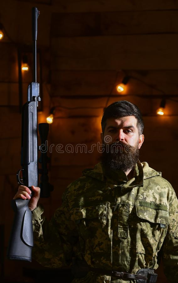 Gamekeeper concept. Hunter, brutal hipster with gun in his hand ready for hunting. Macho on strict face at gamekeepers stock photo