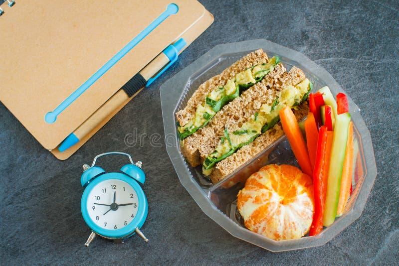 Gamelle avec le sandwich, les légumes, l'eau et les fruits sur le tableau noir photos stock