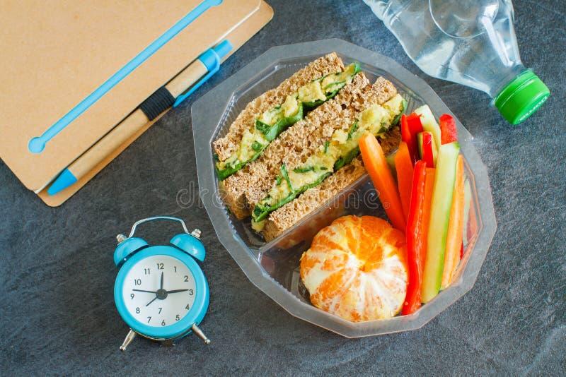 Gamelle avec le sandwich, les légumes, l'eau et les fruits sur le tableau noir photographie stock libre de droits