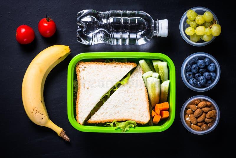 Gamelle avec le sandwich, les légumes, la banane, l'eau, les écrous et les jujubes image libre de droits