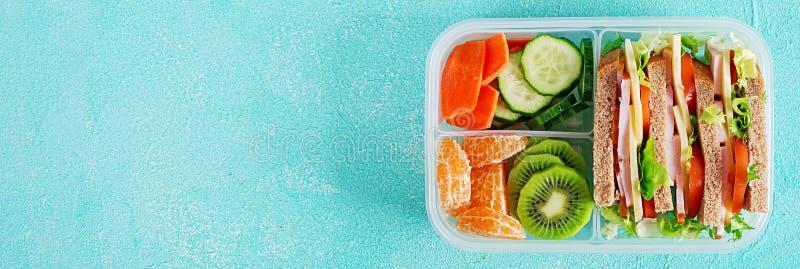 Gamelle d'école avec le sandwich, les légumes, l'eau, et les fruits sur la table images stock