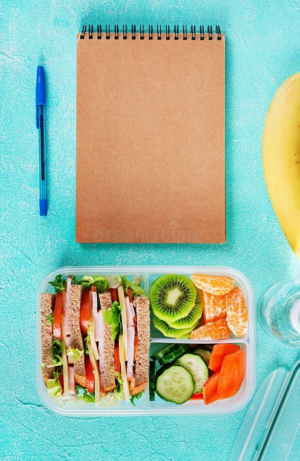 Gamelle d'école avec le sandwich, les légumes, l'eau, et les fruits sur la table photo stock