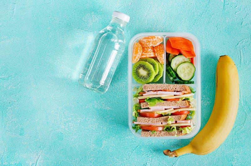Gamelle d'école avec le sandwich, les légumes, l'eau, et les fruits sur la table photos stock