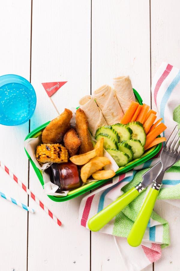Gamelle de pique-nique avec le poulet, les fritures, la tortilla et les légumes photos stock