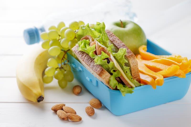 Gamelle saine avec le sandwich, les fruits, les légumes et la bouteille de l'eau sur la table en bois blanche photos libres de droits
