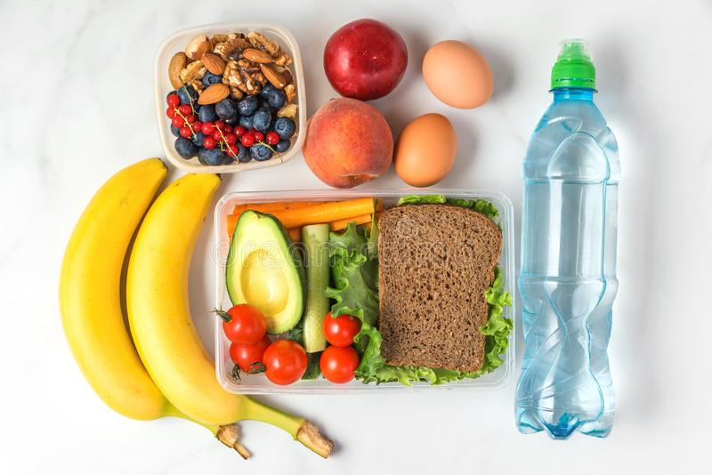 Gamelles d'école avec de l'eau le sandwich, les légumes, les écrous, les baies, la banane, les oeufs, les pêches et sur le fond d image libre de droits