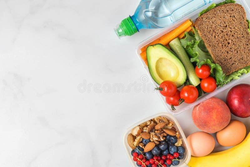 Gamelles saines avec de l'eau le sandwich, les légumes, les écrous, les baies, la banane, les oeufs, l'avocat, les pêches et images stock