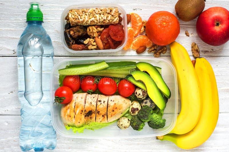 Gamelles saines avec le poulet, les légumes frais, les fruits et les écrous avec la bouteille de l'eau sur le fond en bois blanc photos stock