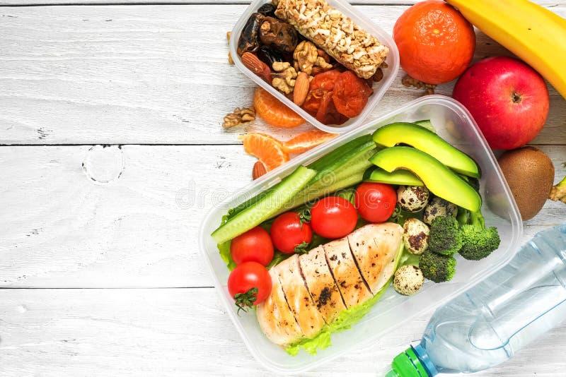 Gamelles saines avec le poulet, les légumes frais, les fruits et les écrous avec la bouteille de l'eau sur le fond en bois blanc photos libres de droits