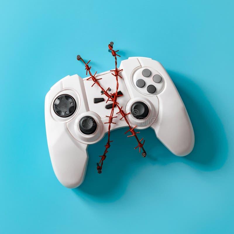 Gamepad με κόκκινο οδοντωτό - καλώδιο Έννοια για το θέμα του ανθρώπινου εθισμού τυχερού παιχνιδιού στοκ εικόνες