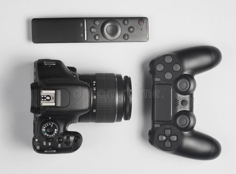 Gamepad, Dslr camera, tv remote. Modern gadgets and devices on gray background.  Top view stock photos