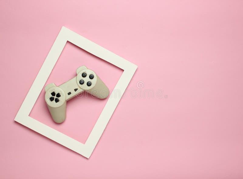 Gamepad i en vit ram på en rosa pastellfärgad bakgrund Bästa sikt, minimalism fotografering för bildbyråer