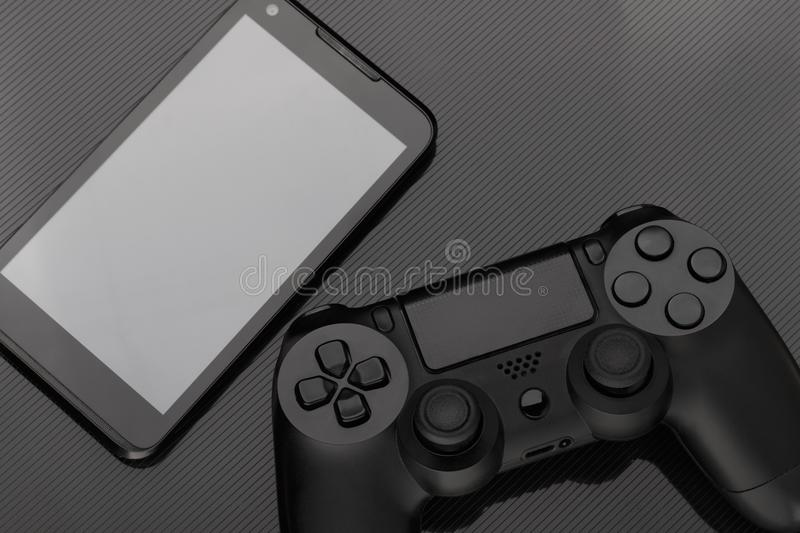 Gamepad and smartphone with blank screen on dark background. stock photo