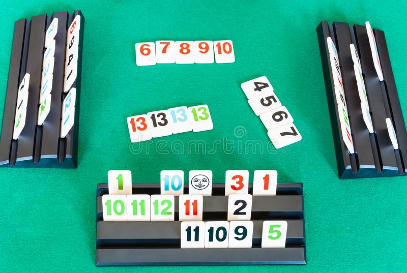 Gameplay of Rummikub tile-based game on table. MOSCOW, RUSSIA - APRIL 3, 2019: gameplay of Rummikub tile-based game on green baize table. Rummikub was invented stock photos