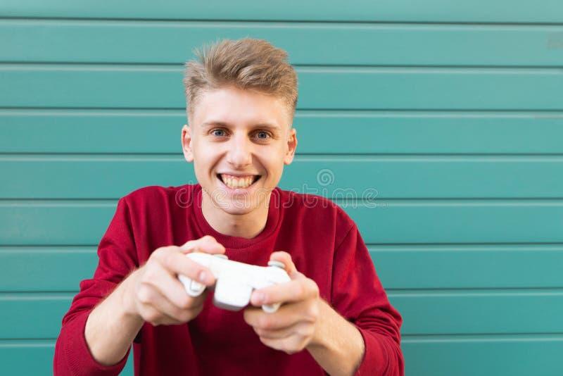 Gamer с gamepad в его руках играет консоль на предпосылке и взглядах бирюзы на камере стоковые фото