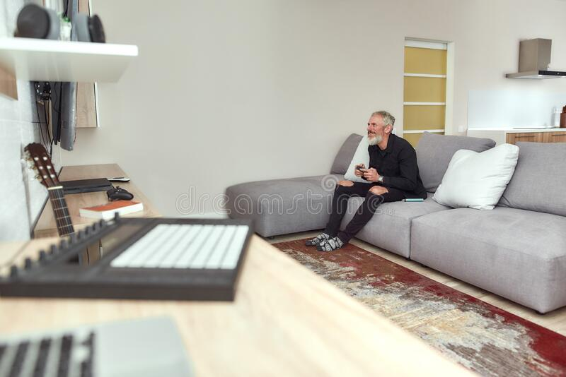Gamer. Bearded middle-aged man, artist holding controller, playing video games, sitting on the couch at home. Weed. Bearded middle-aged man, artist holding stock photo