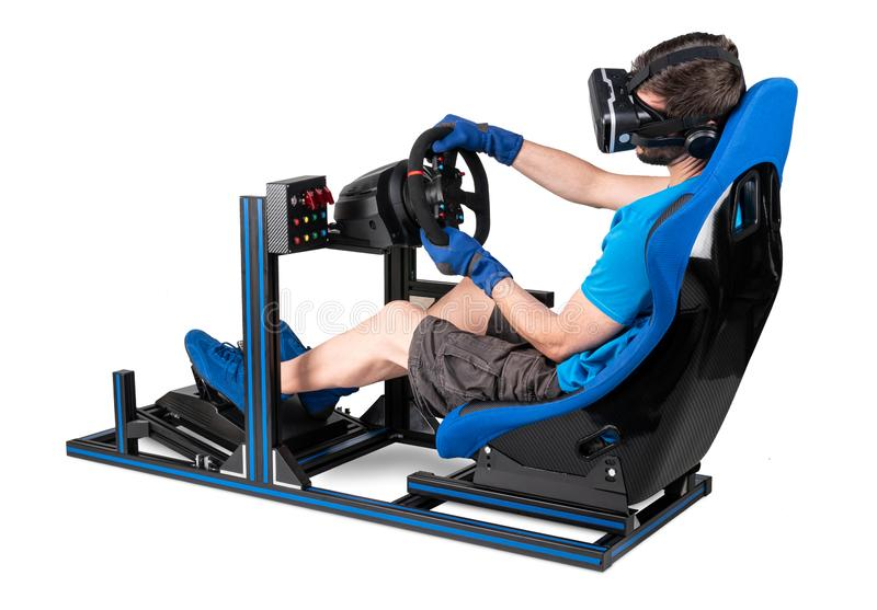 Gamer in blue tshirt with VR virtual reality glasses training on simracing aluminum simulator rig for video game racing. royalty free stock photography
