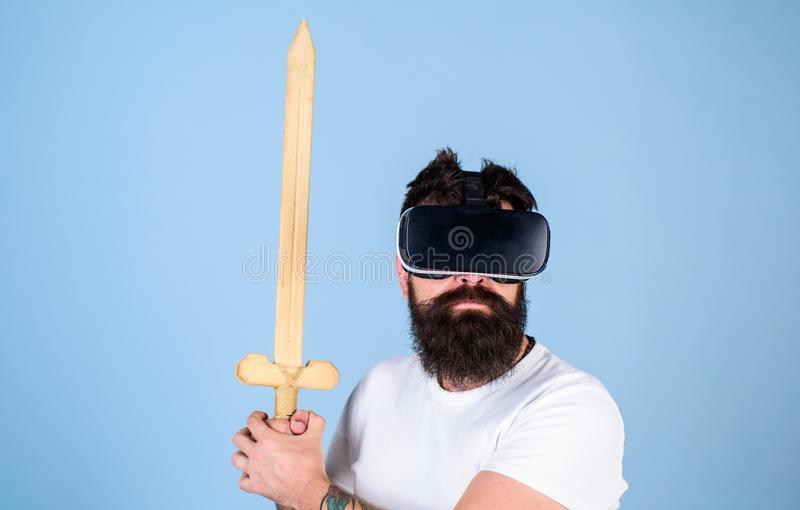 Gamer concept. Hipster on serious face enjoy play game in virtual reality. Man with beard in VR glasses, light blue stock images