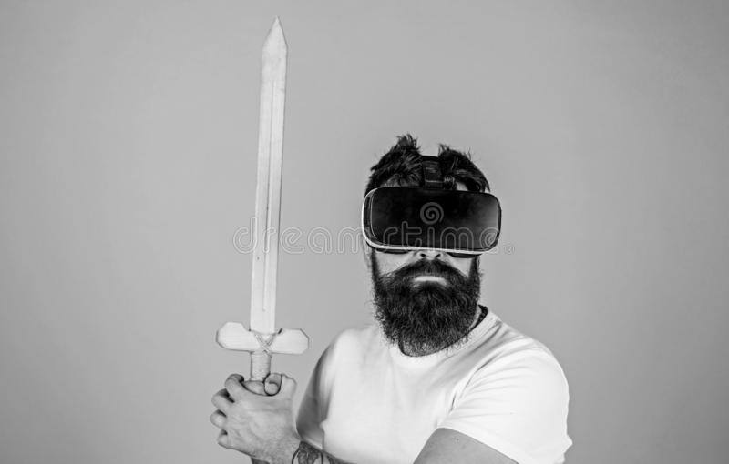 Gamer concept. Hipster on serious face enjoy play game in virtual reality. Man with beard in VR glasses, light blue. Background. Guy with head mounted display stock photography
