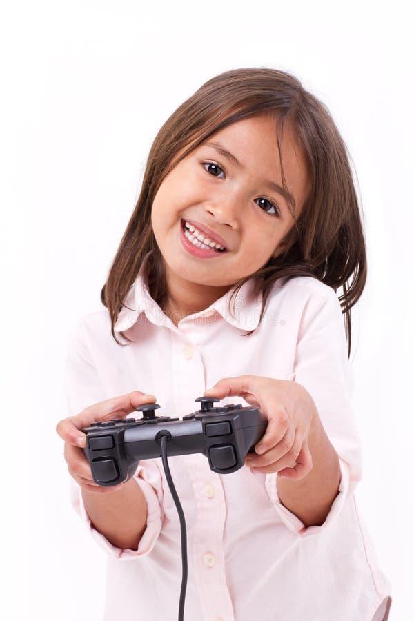 Gamer de petite fille jouant le jeu vidéo photographie stock