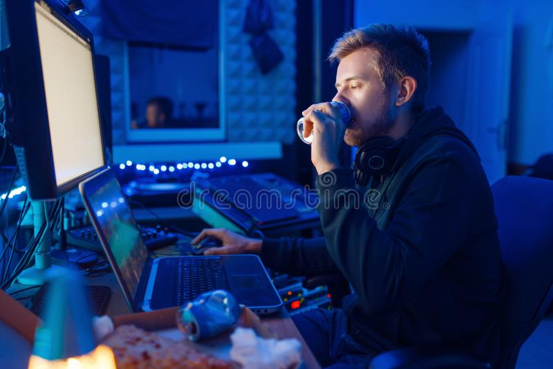 Gamer drinking an energy drink, gaming lifestyle. Male gamer drinking an energy drink at his workplace with laptop and desktop PC, gaming night lifestyle royalty free stock photos
