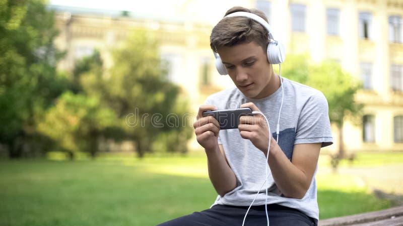Gamer in hoofdtelefoons die in park, speelspel op mobiele telefoon zitten, verslaving stock afbeeldingen