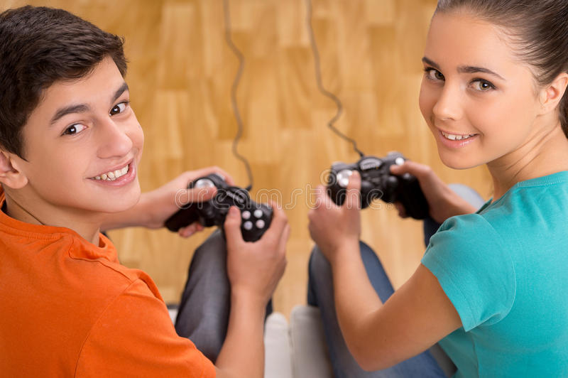 Gamer with joystick. Top view of two young gamers playing video games while sitting on the couch stock image