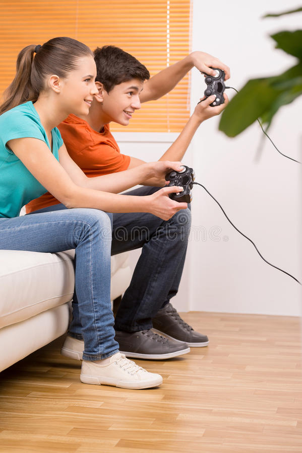 Gamer with joystick. Two young gamers playing video games while sitting on the couch stock photos