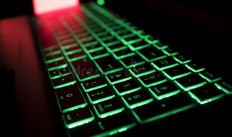Gamer klawiatura z zielonym backlight i czerwieni tłem zaświeca zdjęcia stock