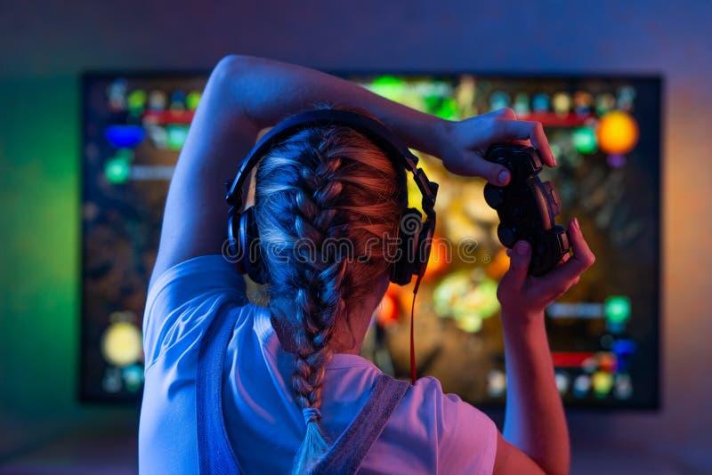 Gamer lub streamer dziewczyna w ciemnym pokoju z gamepad bawić się z przyjaciółmi na sieciach w gra wideo w domu Młody człowiek zdjęcia royalty free