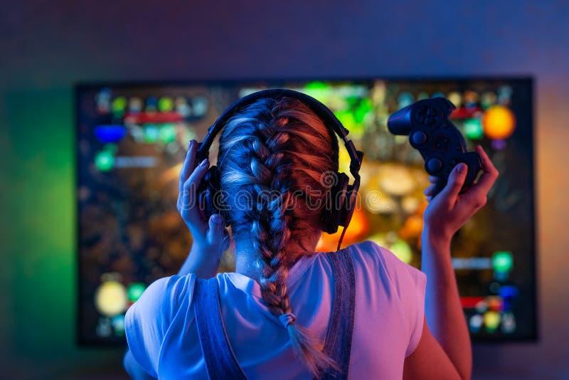 Gamer lub streamer dziewczyna w ciemnym pokoju z gamepad bawić się z przyjaciółmi na sieciach w gra wideo w domu Młody człowiek zdjęcie royalty free
