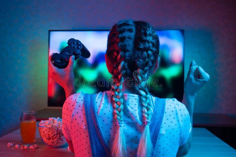 Gamer lub streamer dziewczyna w ciemnym pokoju z gamepad w domu, bawić się z przyjaciółmi online w gra wideo z popkornem i fotografia royalty free