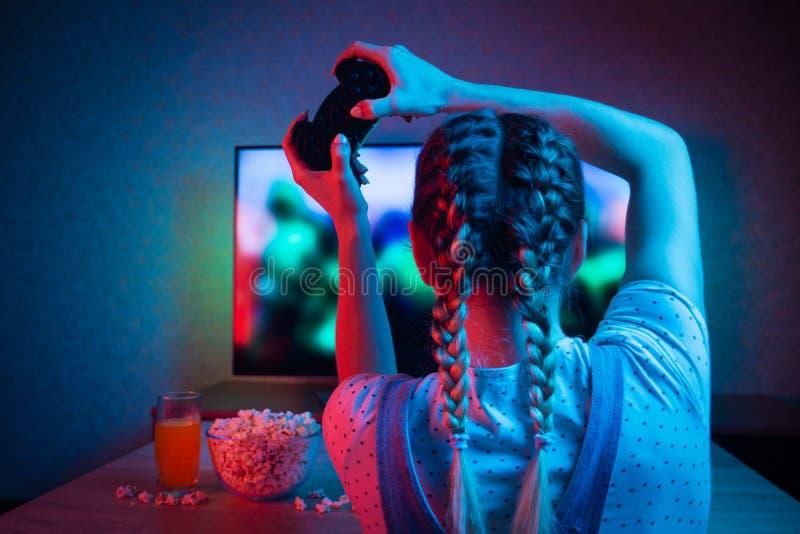Gamer lub streamer dziewczyna w ciemnym pokoju z gamepad w domu, bawić się z przyjaciółmi online w gra wideo z popkornem i zdjęcia stock