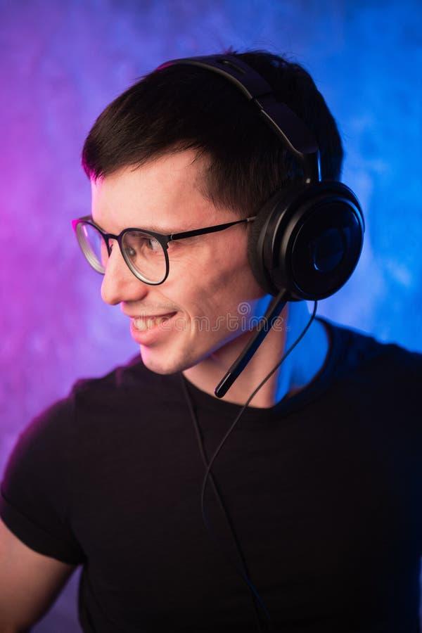 Gamer lub streamer w słuchawkach z mikrofonem nad kolorowymi menchiami i błękitną neonową zaświecającą ścianą zdjęcie stock
