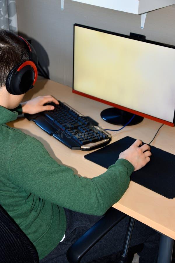Gamer lub streamer w słuchawkach z mikrofonem siedzimy w domu w ciemnym pokoju i sztukach z przyjaciółmi na sieciach obraz stock