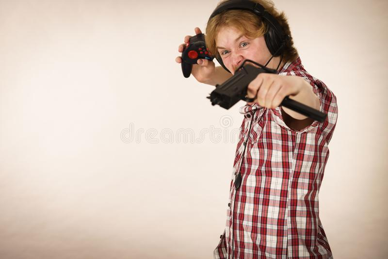 Gamer man shooting from gun. Nerd geek young adult man playing on the video console holding gun wearing headphones with microphone. Gaming gamers concept stock images