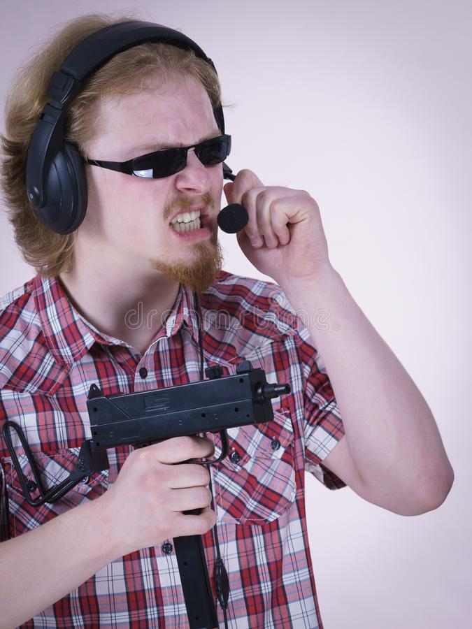 Gamer man shooting from gun. Nerd geek young adult man playing on the video console holding gun wearing headphones with microphone. Gaming gamers concept stock photography
