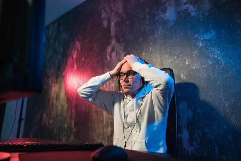 Gamer novo engraçado com uns auriculares que jogam jogos de vídeo em um computador e olhares na tela com a admiração Retrato fotos de stock