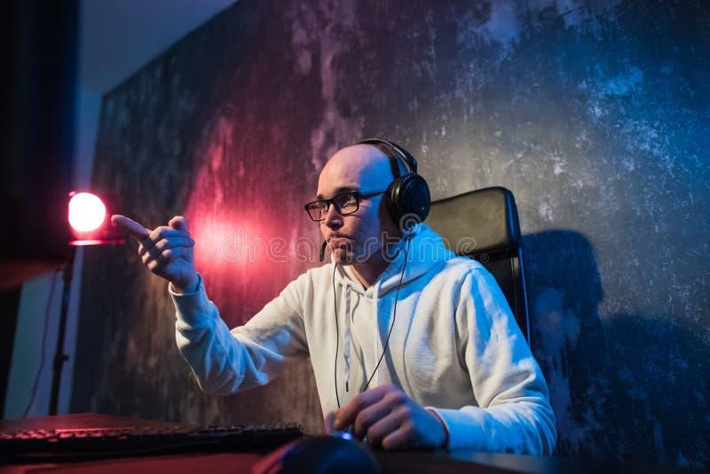 Gamer novo engraçado com uns auriculares que jogam jogos de vídeo em um computador e olhares na tela com a admiração Retrato fotografia de stock