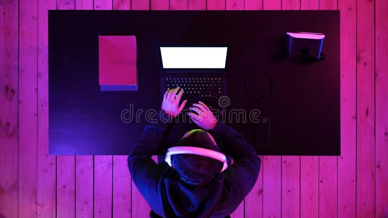 Gamer novo que joga o fones de ouvido vestindo do jogo de vídeo Indicador branco imagem de stock