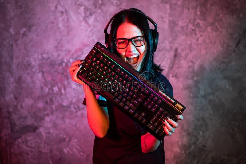 Gamer professionnel de fille en jeu vidéo de stratégie de MMORPG Elle est elle posant au-dessus du fond bleu et rose coloré avec  images stock