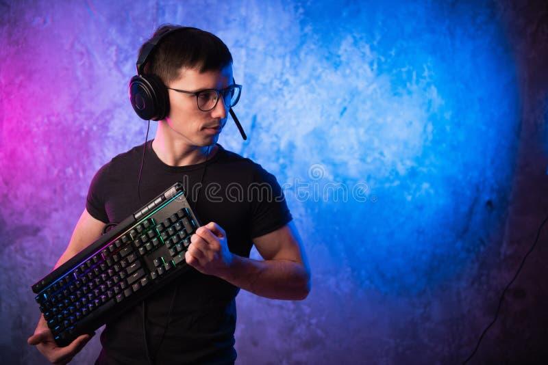 Gamer profissional do menino que guarda o teclado do jogo sobre o rosa colorido e a parede leve de néon azul Conceito dos gamers  imagens de stock