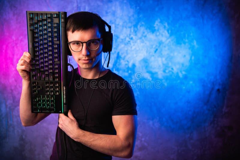 Gamer profissional do menino que guarda o teclado do jogo sobre o rosa colorido e a parede leve de néon azul Conceito dos gamers  fotografia de stock