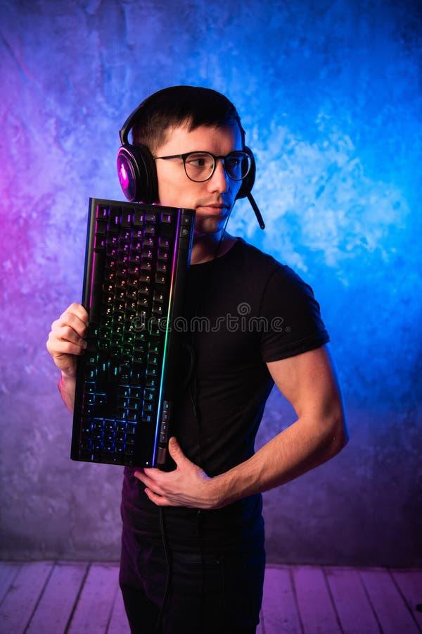 Gamer profissional do menino que guarda o teclado do jogo sobre o rosa colorido e a parede leve de néon azul Conceito dos gamers  foto de stock royalty free