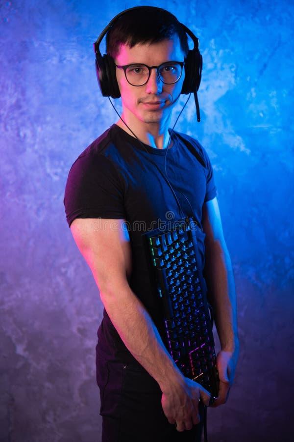 Gamer profissional do menino que guarda o teclado do jogo sobre o rosa colorido e a parede leve de néon azul Conceito dos gamers  imagens de stock royalty free