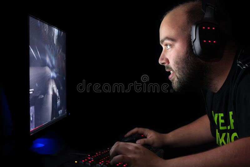 Gamer que joga um primeiro atirador da pessoa no PC da parte alta