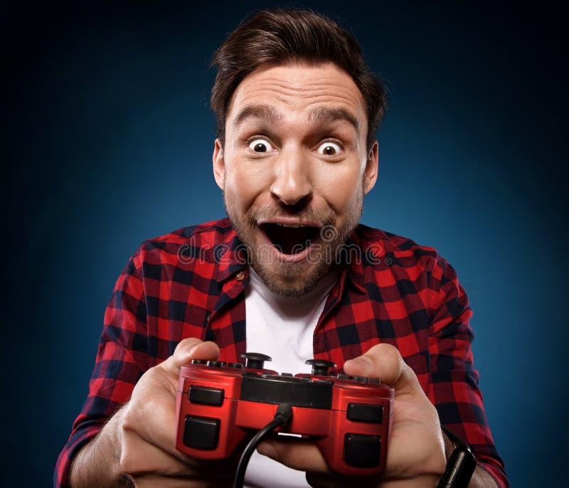 gamer speelt een videospelletje met zijn rode bedieningshendel royalty-vrije stock afbeelding